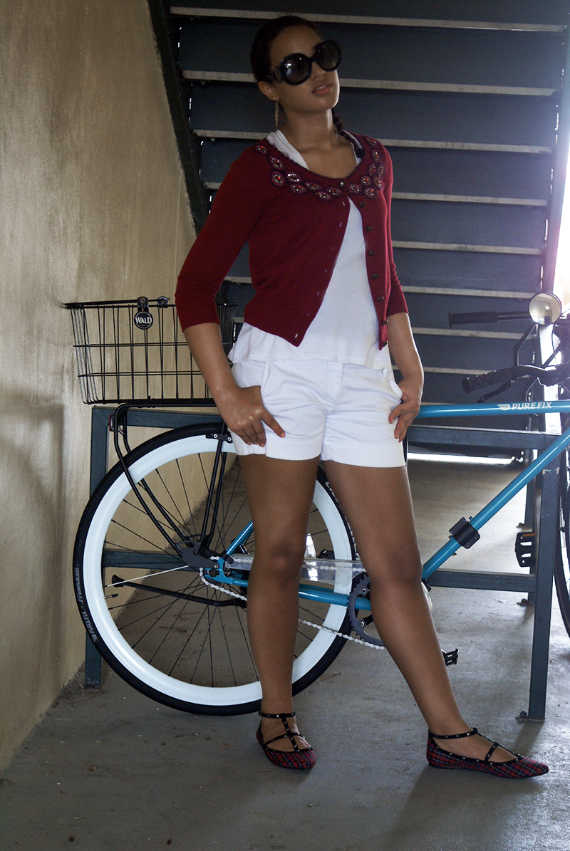 Girl in red, jeweled cardigan with bike