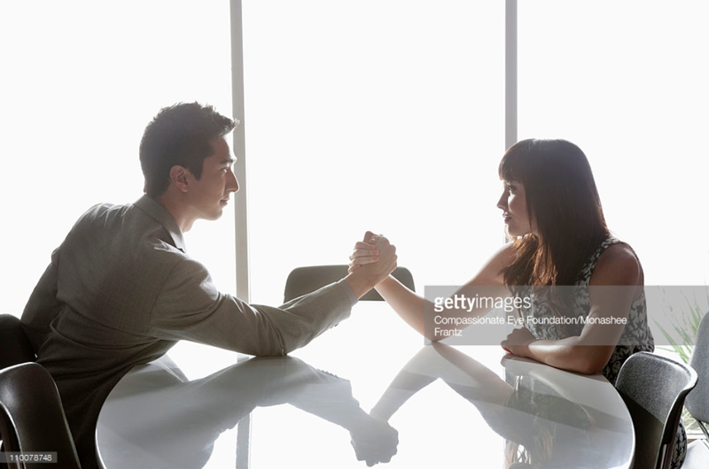 Man and Woman arm wrestling. Compassionate Eye Foundation -110078748. gettyimages.com